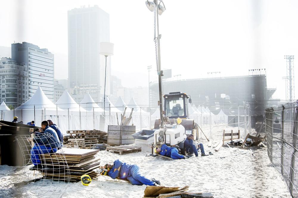 Några arbetare tar en vilopaus på Copacabana. De jobbar med att slutföra uppbyggnaden av OS-området där beachvolleybollen spelas.