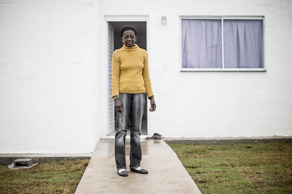 Denise står framför sitt nya hus som är betydligt mindre än det förra som bara låg hundra meter bort men ansågs för ruffigt för att stå kvar.