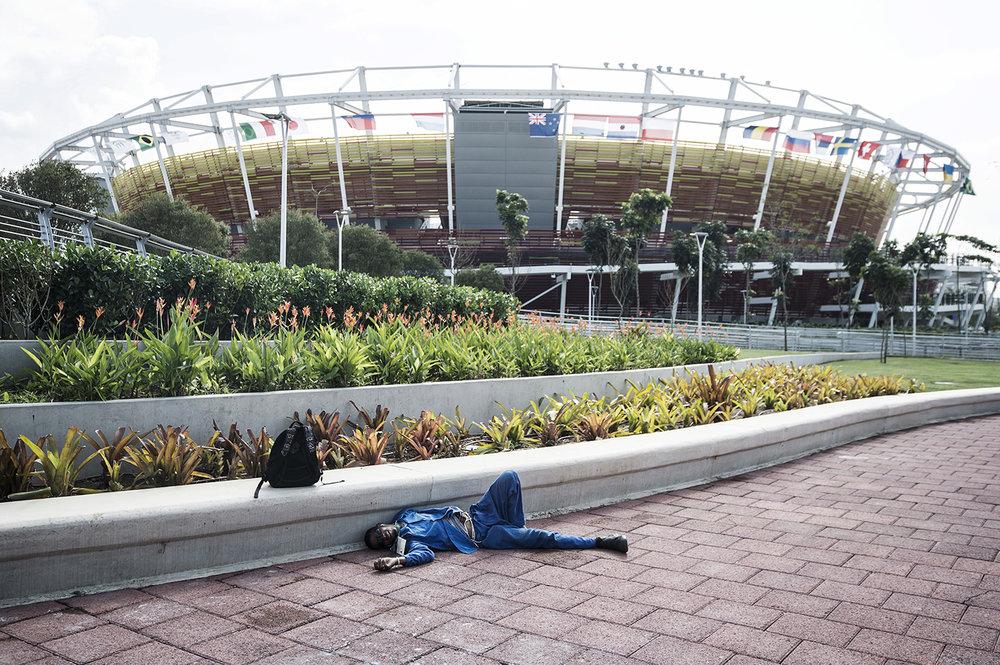 En arbetare har sökt sig till skugga i os-parken i Rio de Janeiro, där de Olympiska spelen börjar om 6 dagar Arbetspassen för arbetarna som ska slutföra uppbyggnaden av arenorna är ofta långa och med dåliga villkor.