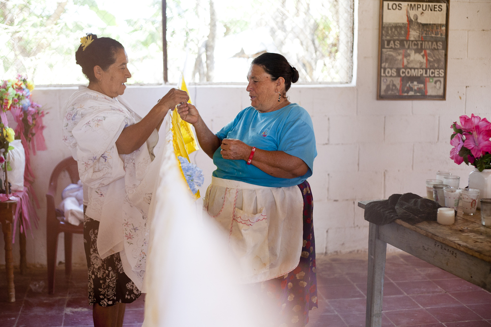 "Women prepare for the community center for a religious celebration. Over  half of El Salvador's residents are Roman Catholic, and much of the  country makes a pilgrimage to the capital city of San Salvador for a  weeklong celebration of ""El Salvador del Mundo,"" or Jesus the Savior of  the World."