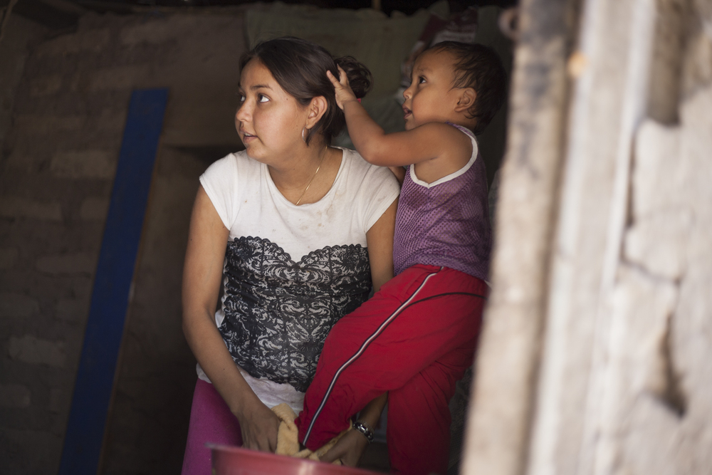 Ivania, 19, bathes her son Antony, 3, in their Amatitán home. Ivania  requires dialysis for a chronic disease and was selected by ACD to have a  special room built for her treatments, where they can be perfomed  without risk of contamination.