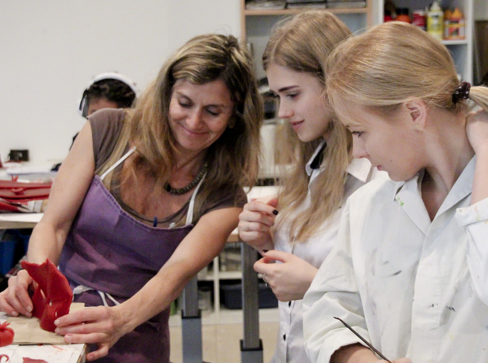 Gabriela Spector works with TASIS students sculpting in wax before sending the pieces to the foundry.