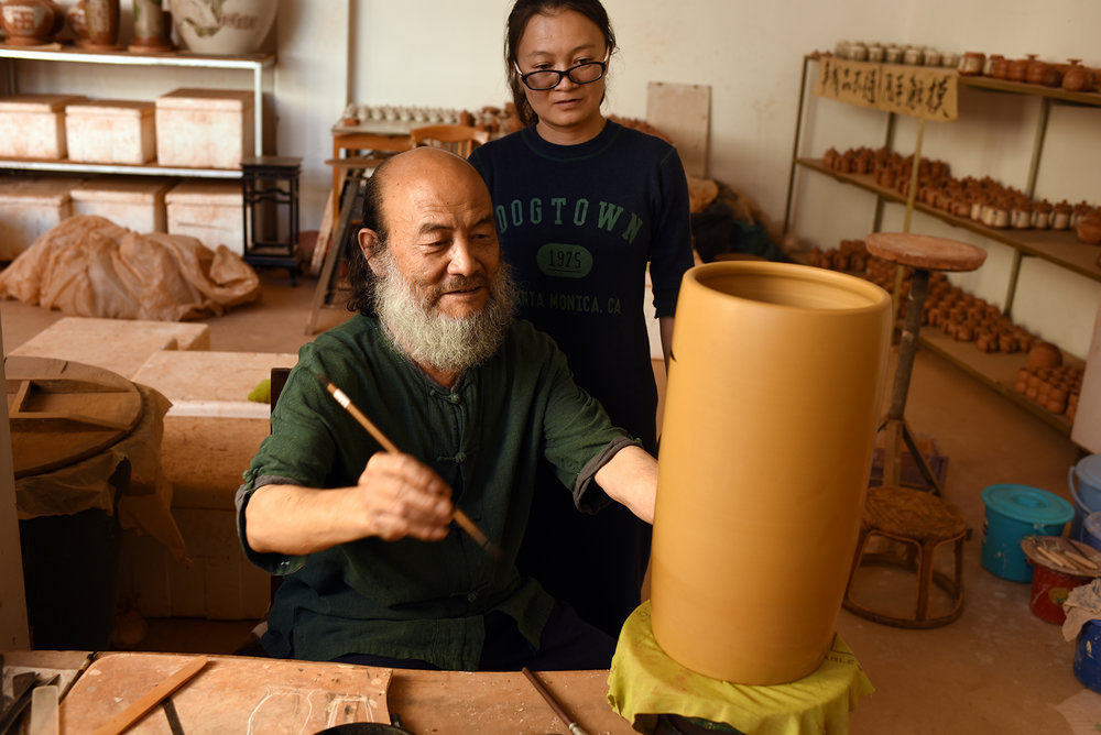 Tan Zhi Fan, Inheritor of Purple Pottery Intangible Cultural Heritage, with his daughter. Jianshui, Yunnan Province.