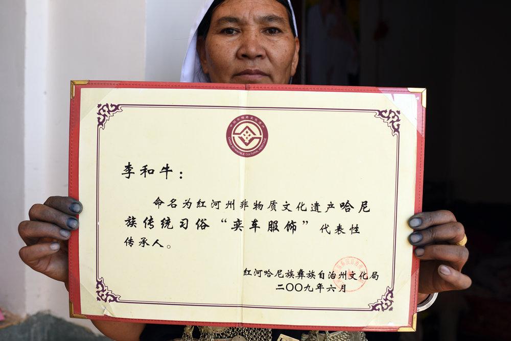 Li He Niu shows the her intangible cultural heritage inheritor certificate.  Dayangjie town, Yunnan 2017.