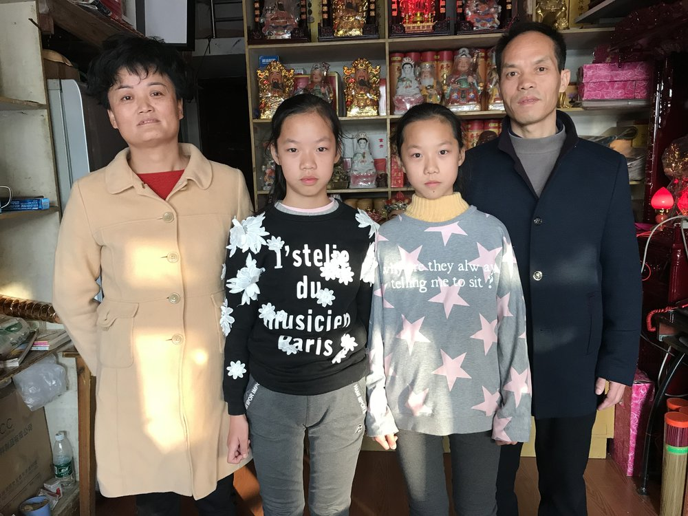Mother, Zhu Yuan e, and father Xin Xian Shou, with their daughters inside the incense shop, 2017.