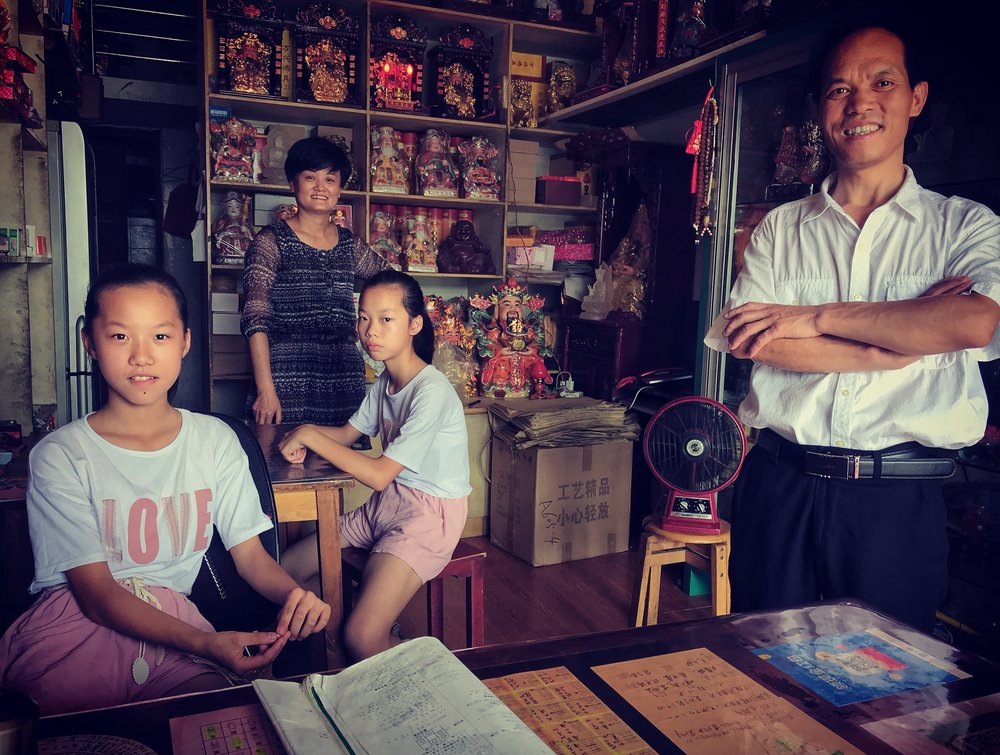 Mother, Zhu Yuan e, and father Xin Xian Shou, with their daughters inside the incense shop, 2018.