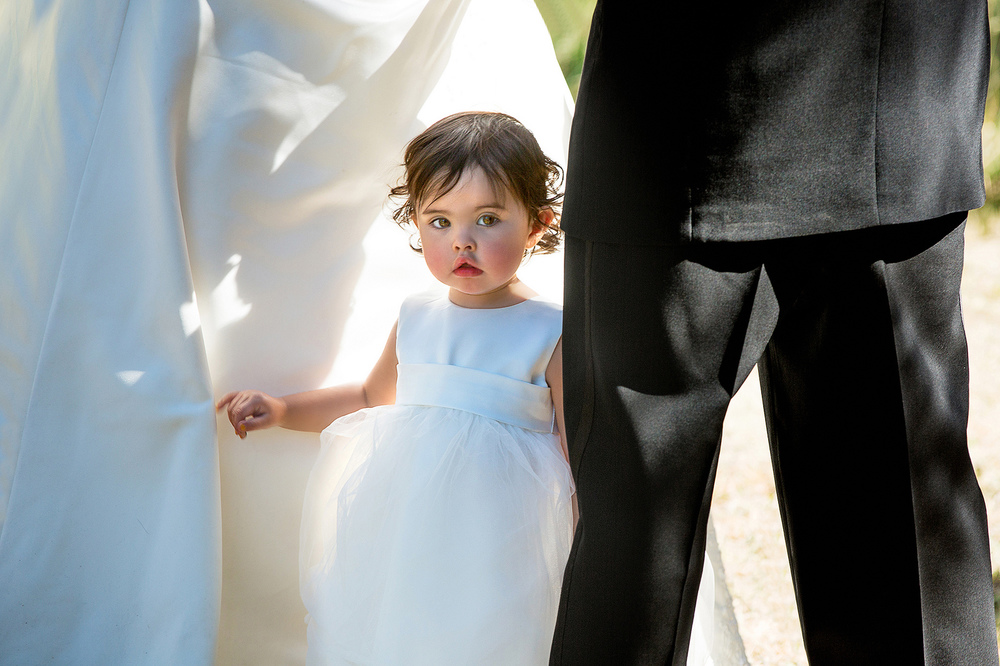 A little girl hides between his mother and father during their wedding service in Zortman, Montana.