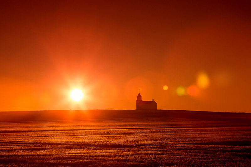 The former Bethany Lutheran Church, now abandoned, sits high atop the Montana plains north of Dunkirk as the rising sun back lights it and creates a wonderful silhouette and adds some lens flare at the same time.  → Buy This Print