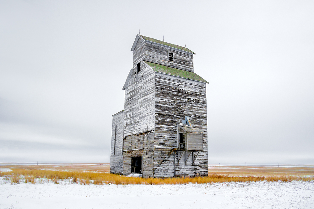 An old grain elevator stands watch over the cold, snow-covered Montana plains outside of the small town of Rudyard. It was -22 degrees Fahrenheit on the morning this photograph was taken. Just another day on the Hi-Line.   → Buy This Print