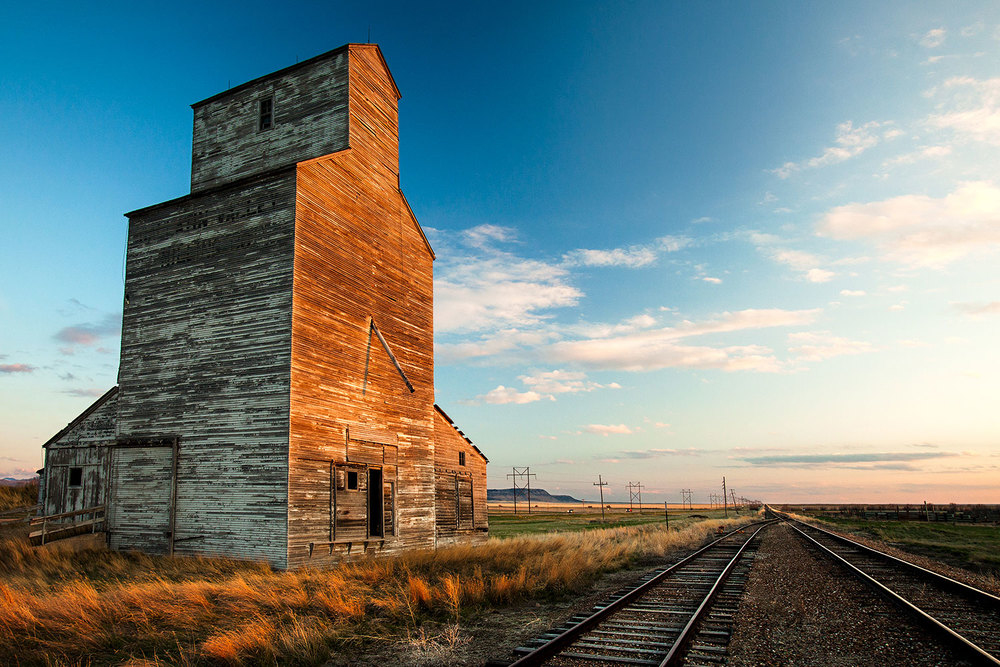 The day's last light illuminates the side of an old grain elevator in the old railroad town known as Laredo, Montana.   → Buy a Print