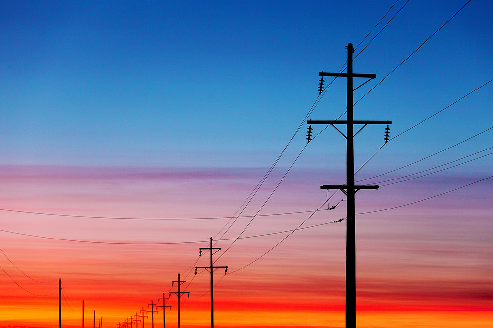 The sunrise to the ease silhouettes this row of electrical poles and power lines near Fairfield, Montana. → Buy a Print