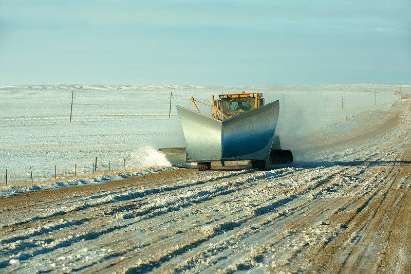 A snow plow removes snow after the big storm from a rural gravel road in southern Chouteau County, Montana. → License Photo.