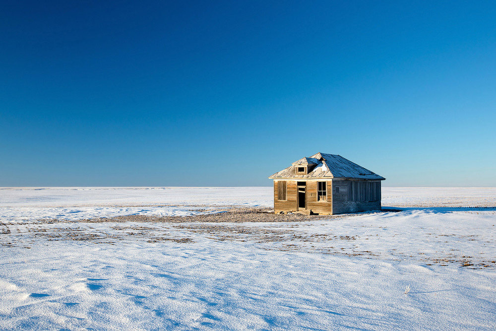 An old, broken-down house surrounded by the vastness of Montana's eastern plains. → Buy a Print