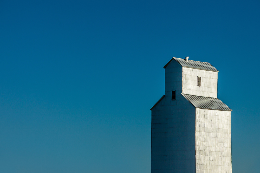 A solitary grain elevator shrouded in sheet metal against a steel blue sky in Gildford, Montana.   → Buy a Print