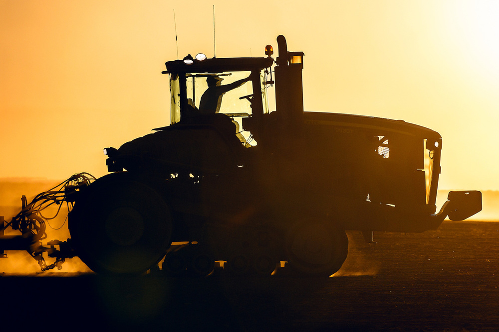 A silhouette of a John Deere tractor seeding wheat on a farm near Chinook, Montana.   → License Photo