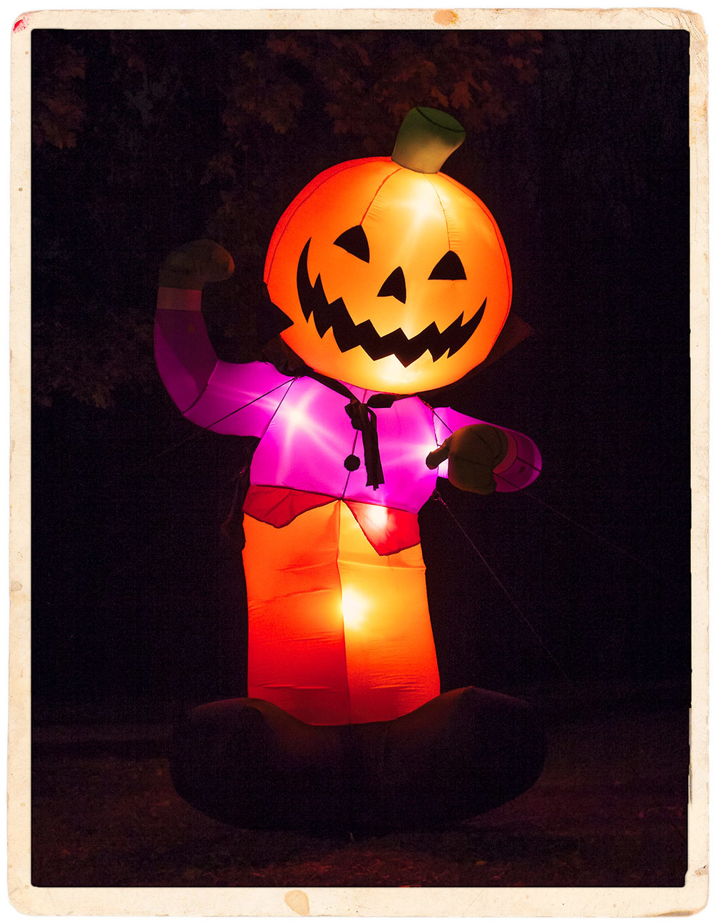 An inflatable jack-o'-lantern man and Halloween display in a yard photographed at night.