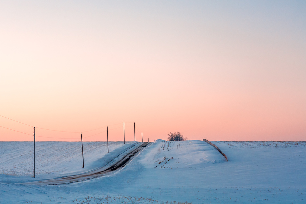 A quiet country road lined with telephone poles and a snow fence before the sun crests the horizon on a cold wintry morning. → Buy a Print