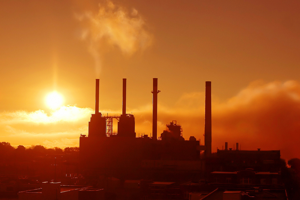 An electric plant releases some steam on a chilly autumn morning against a bright sunny sky.     → License Photo