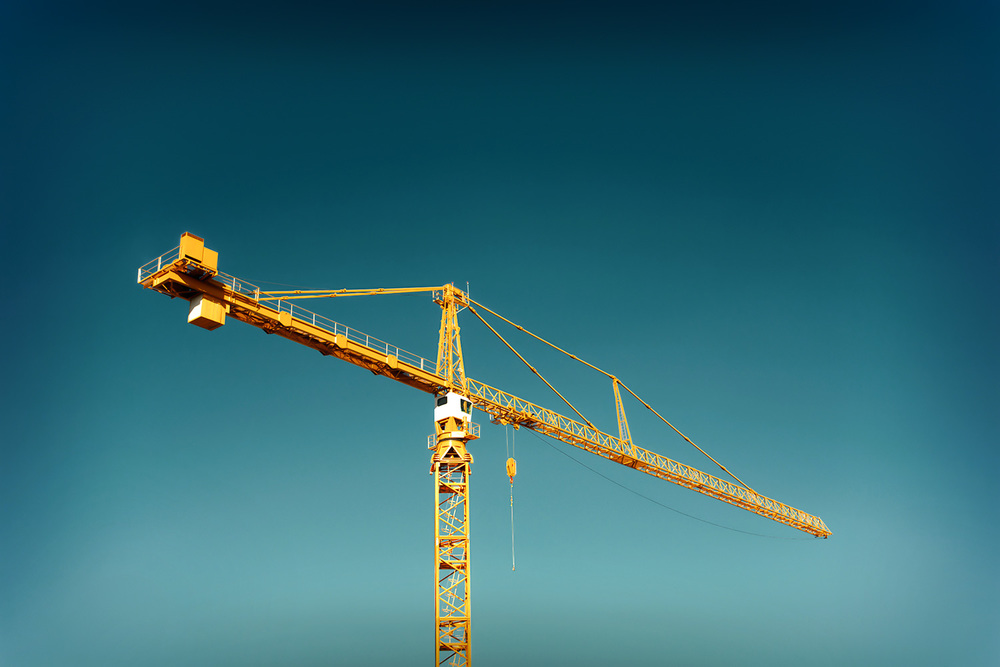 A bright yellow hammerhead tower crane stands alone against a perfectly clear blue sky.     → License Photo