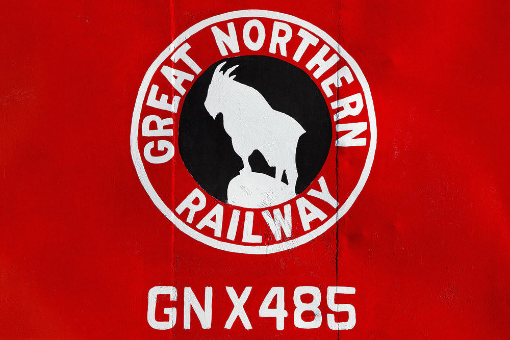 A close-up of the Great Northern Railway logo on the side of a red caboose in Havre, Montana. → Buy a Print