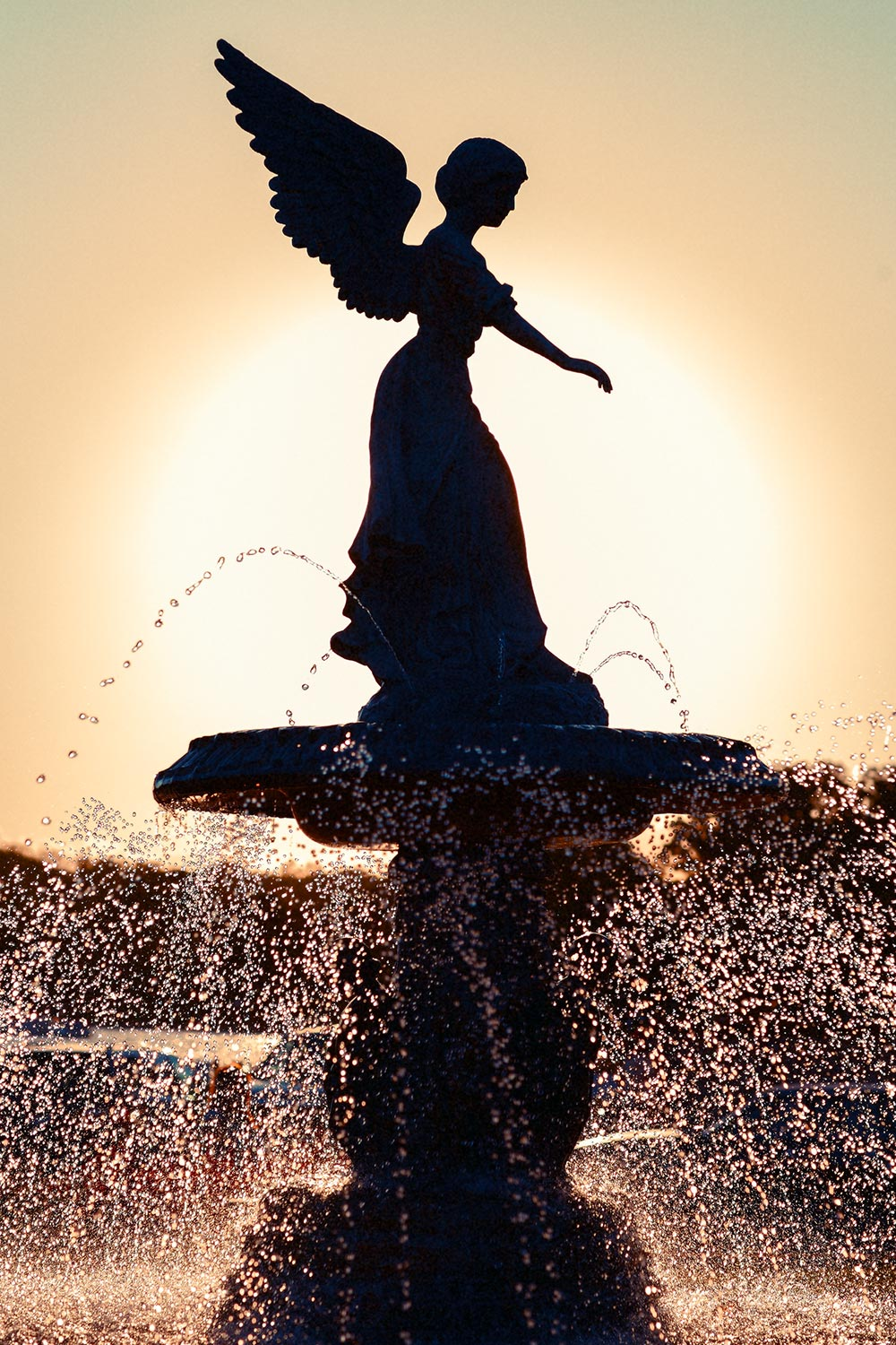 A silhouette of the fountain and droplets of water at Rivera Beach along the lake shore in Lake Geneva, Wisconsin. → Buy a Print
