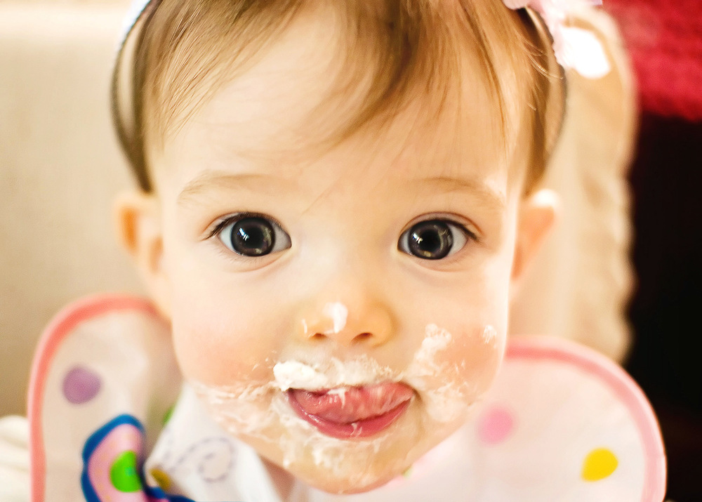 A photograph of my niece Amber enjoying a taste of cake at her first birthday party.