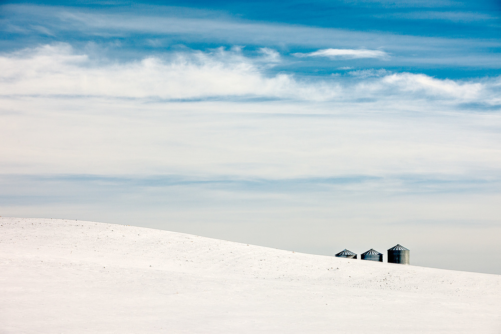 A trio of grain bins lurk over the horizon on what is an otherwise bleak, snowy landscape near Big Sandy, Montana. → Buy a Print or License Photo