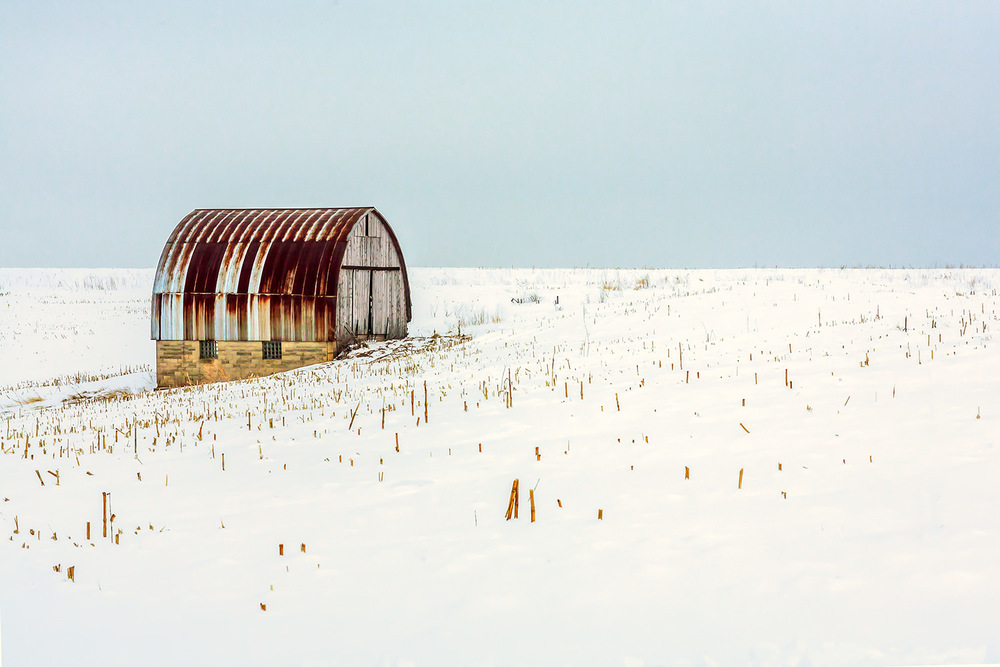 An old barn with a red, rusty roof stands alone and abandoned on a snowy landscape outside of Monroe, Wisconsin. → Buy a Print
