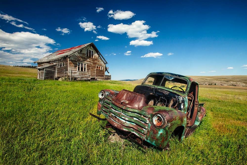An old house and a rotting jalopy near Lingshire, Montana. → Buy a Print or License Photo