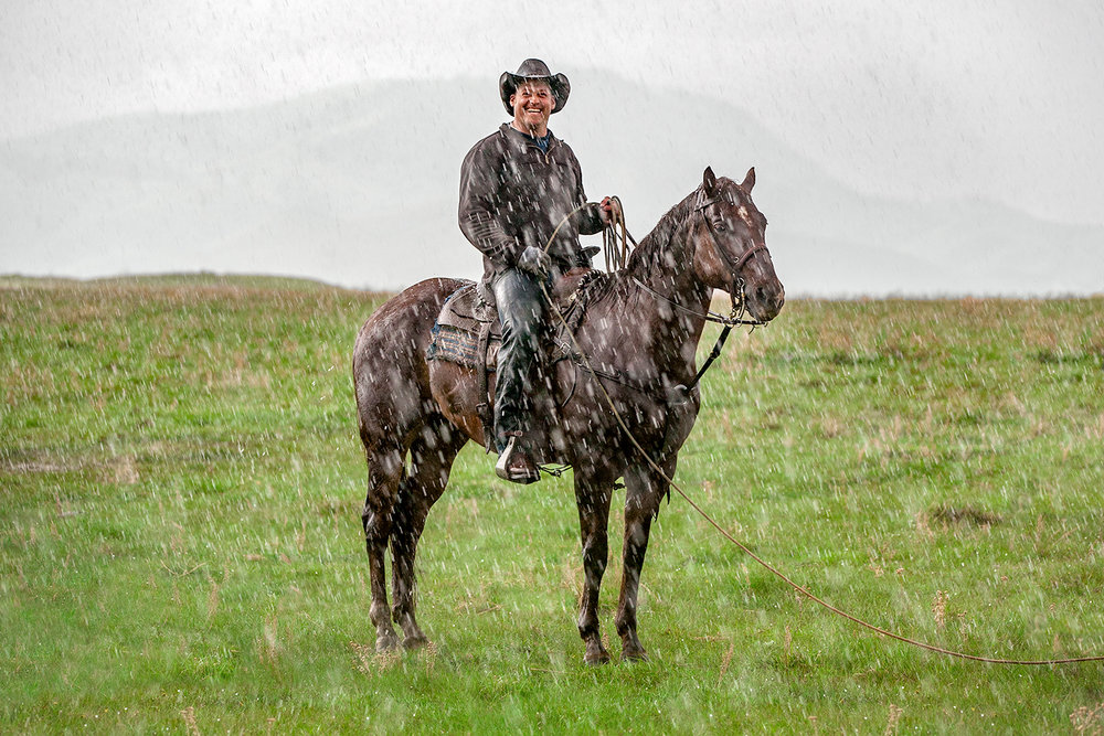 Cowboy Riding Horse in the Rain Smiling