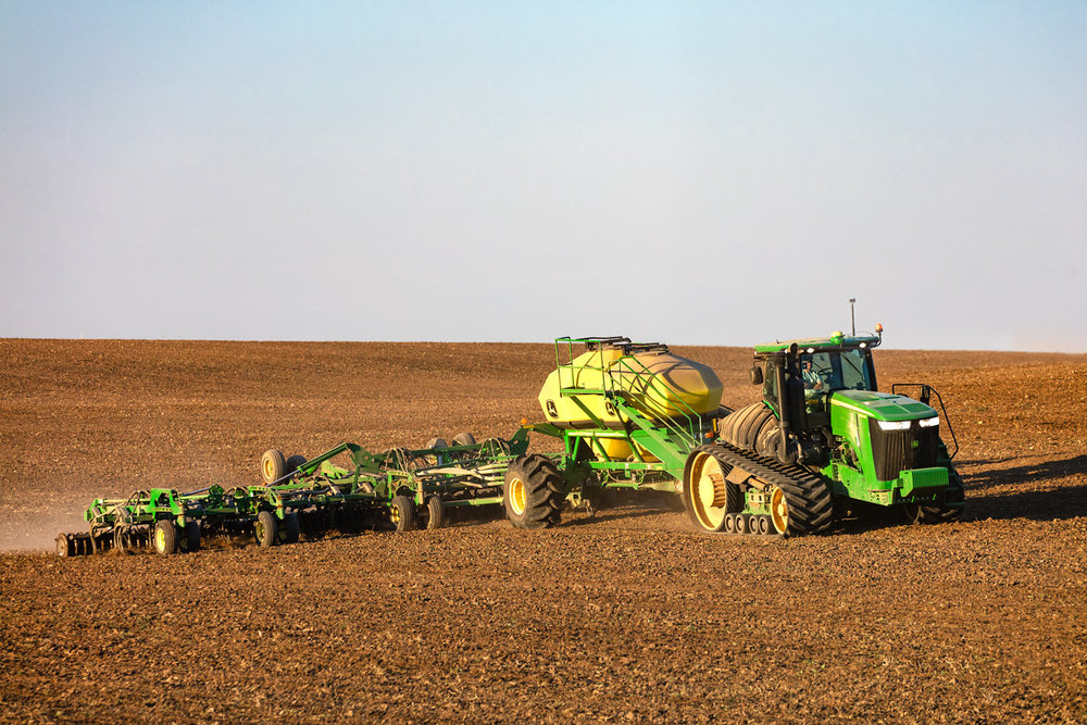A farmer seeds wheat on an organic farm with a John Deere tractor and air drill south of Chinook, Montana.