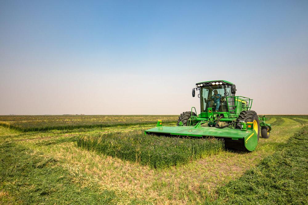 A John Deere 995 self-propelled hay windrower cutting alfalfa on a farm near Valier, Montana.