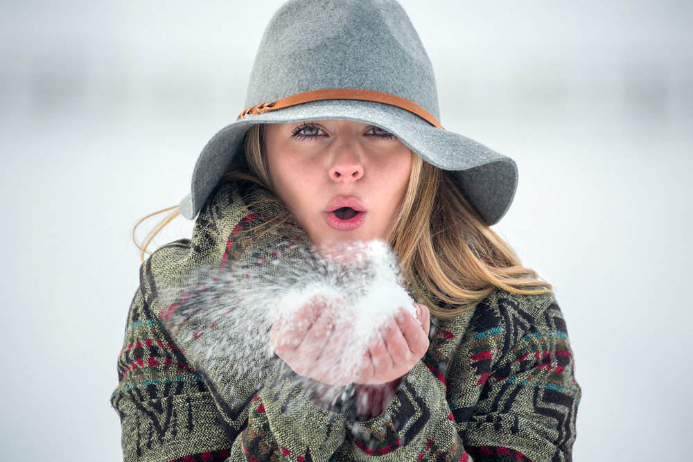 A cowgirl photo of a young woman blowing snow from her hands on a cold winter day outside of Four Corners, Montana.