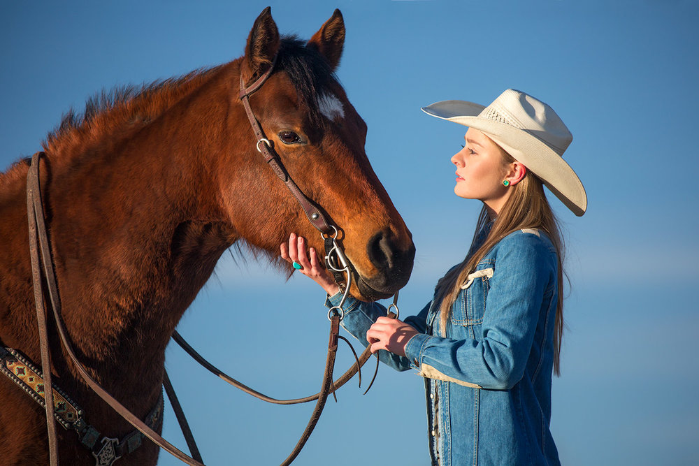 Another cowgirl photo of a young woman petting her horse on a ranch near Bozeman, Montana.