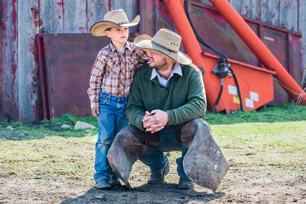 A cowboy father and son take a break from the action on a ranch near Chinook, Montana.   → License Photo