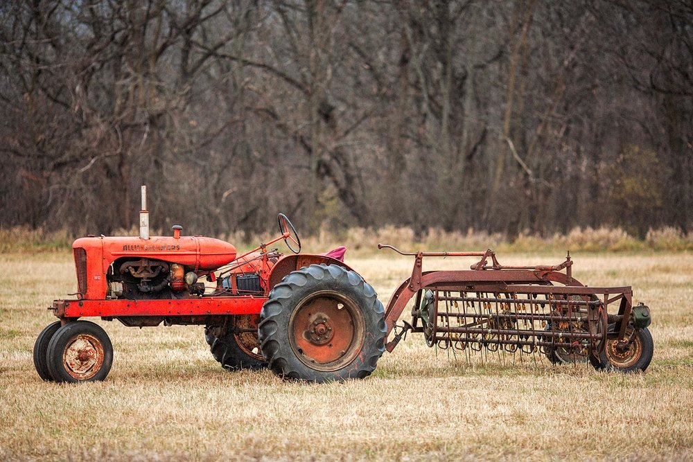 An old Allis-Chalmers WD tractor hitched to a hay rake near New Glarus, Wisconsin.   → License Photo