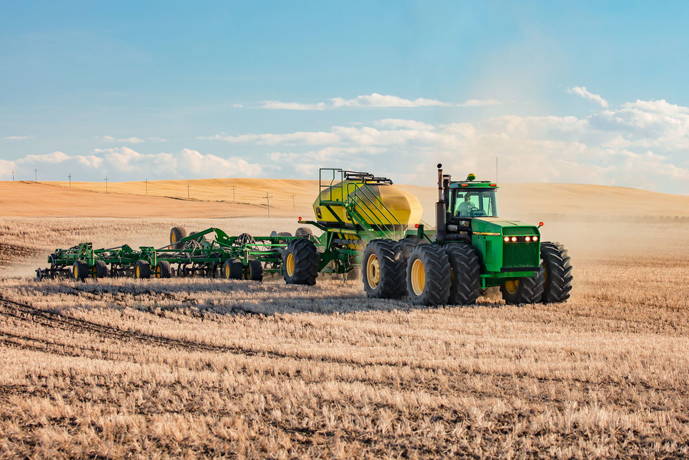 A John Deere 8970 tractor pulling an air drill while seeding wheat near Conrad, Montana.   → License Photo