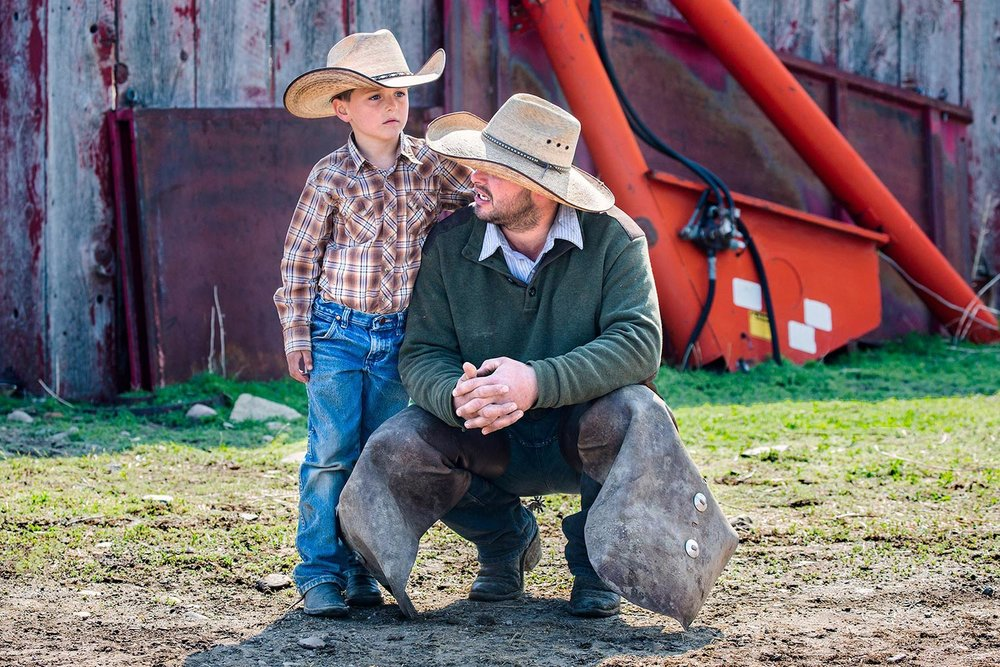 Ethan Klingman and his father Larry take a break in the action on branding day on the Gordon Cattle Company ranch near Chinook.   → License Photo