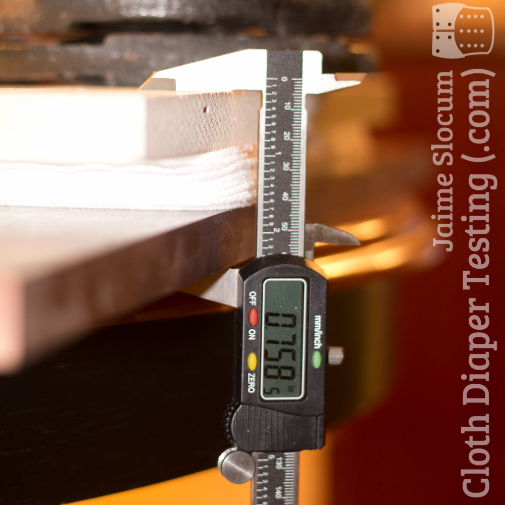 The caliper measuring the thickness of the stacked layers of insert fabric, with 15 lbs of weight adding moderate compression.