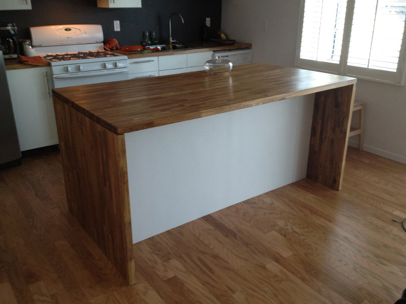 """For the face of the island, we attached a piece of 1/2"""" plywood to the 2x4 base and the back of the cabinets. We then used a sheet of vinyl wall panel (called Plas-Tex)that we picked up at Lowe's. It is attached with liquid nail, that's it. So far, its held up well. Easy to clean kick marks too!"""