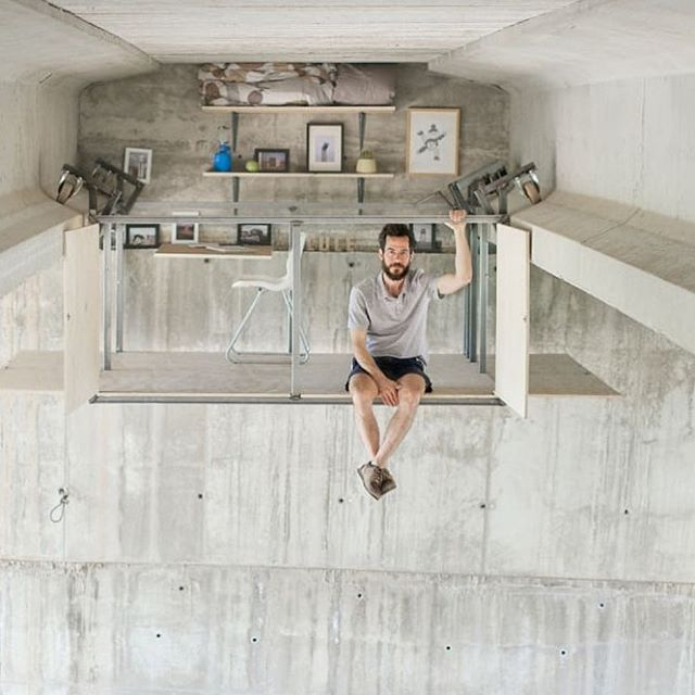 """Have you seen this amazing secret studio? This designer, Fernando Abellanas, built his own studio that hangs beneath an underpass in Valencia, Spain: """"Self-taught furniture designer Fernando Abellanas has transformed the underside of a bridge in Valencia, Spain, into an ingenious, pop-up workspace. Abellanas's design is half floating studio, half horizontal elevator. One part is a metal and plywood box that moves across the underside of the bridge on wheels. When it gets to the far side, a shelf, chair, and desk bolted into the wall fit into the structure to complete the studio."""" Amazing! Via co.design [Image: Lebrel] #urbandesign #secretstudio #urbanunderpass #hiddengem"""