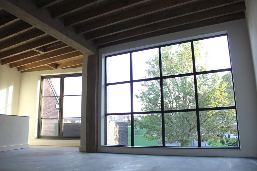 De betonnen vloer, de grote raampartijen en de houten plafonds zijn bepalend voor de industriële maar warme sfeer