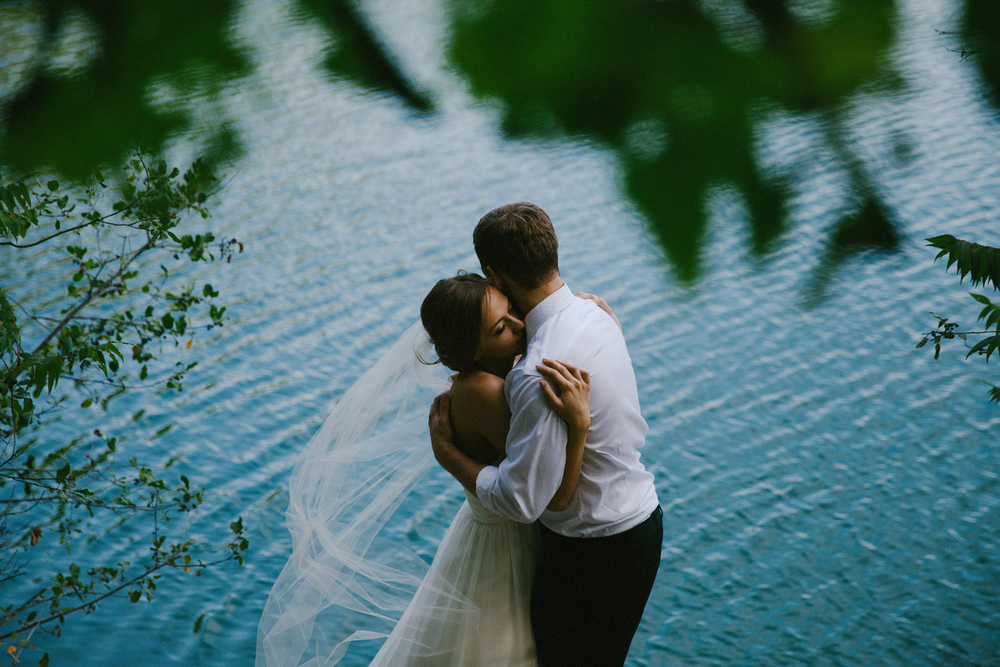 Bride and groom embrace by Pink Lake in Gatineau Park