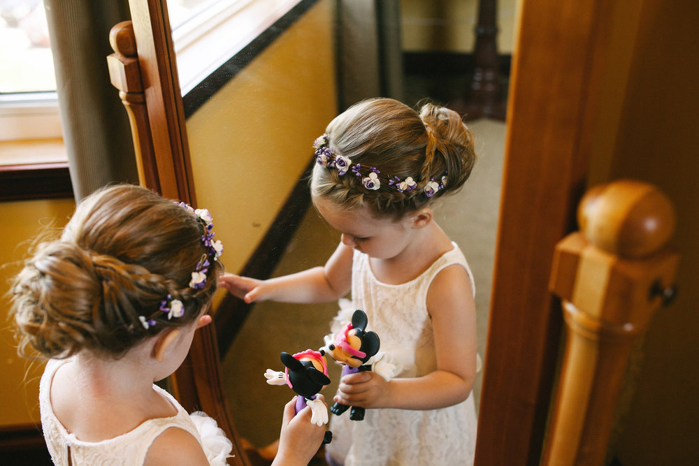 Flower girl plays with mirror and toys