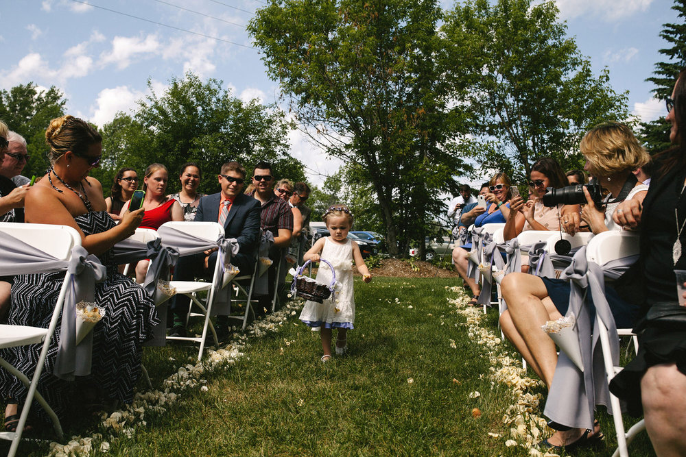 Flower girl dropping petals at outdoor wedding
