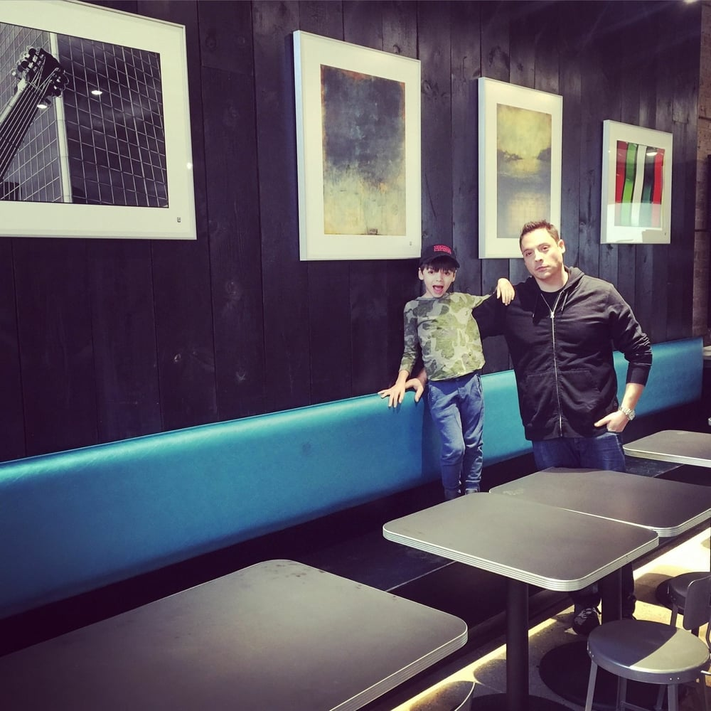 Jeff Mauro and his son Lorenzo standing in front of my two framed prints at Pork and Mindy's (repost from @jeffmauro)