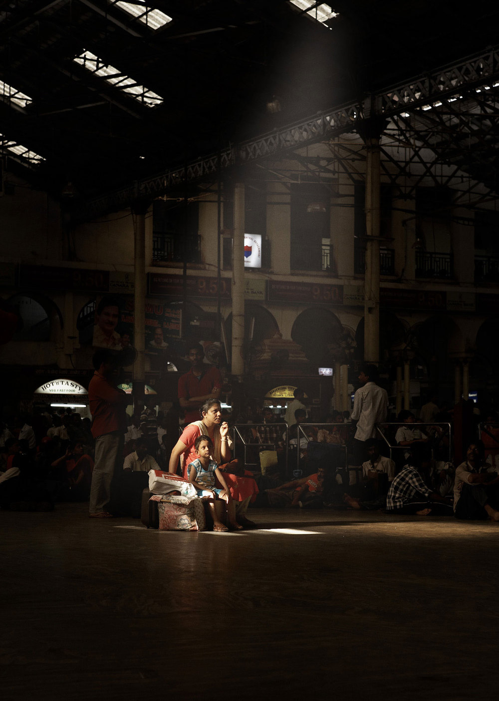 Mother and daughter in a ray of light. Chennai Central Railway Station, India.