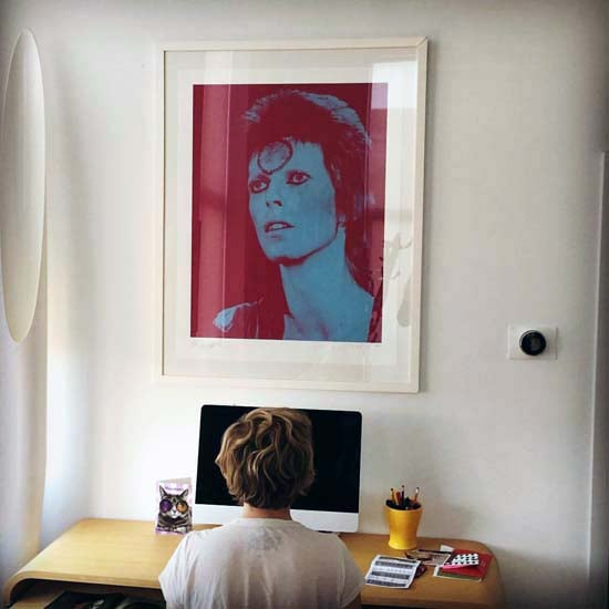 Author Lori Majewski at her desk under her Bowie portrait by Mick Rock