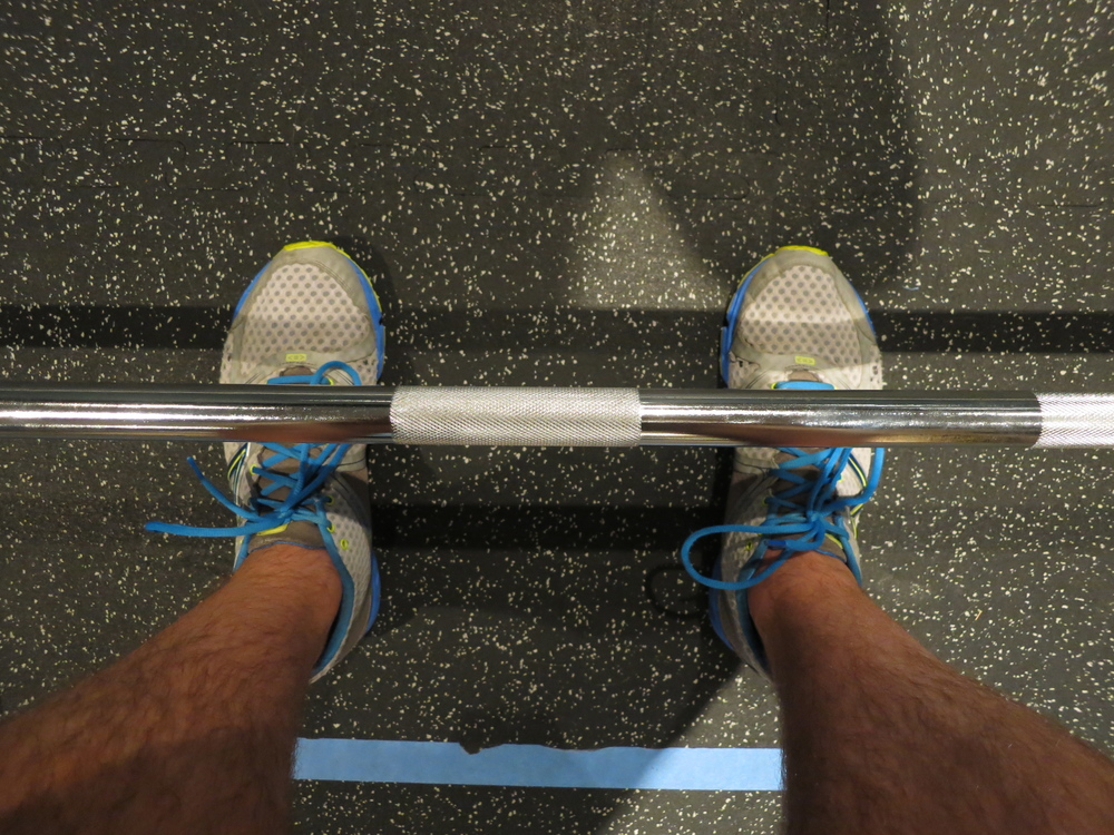 When viewing the barbell from directly overhead, the barbell should line up with your mid foot.