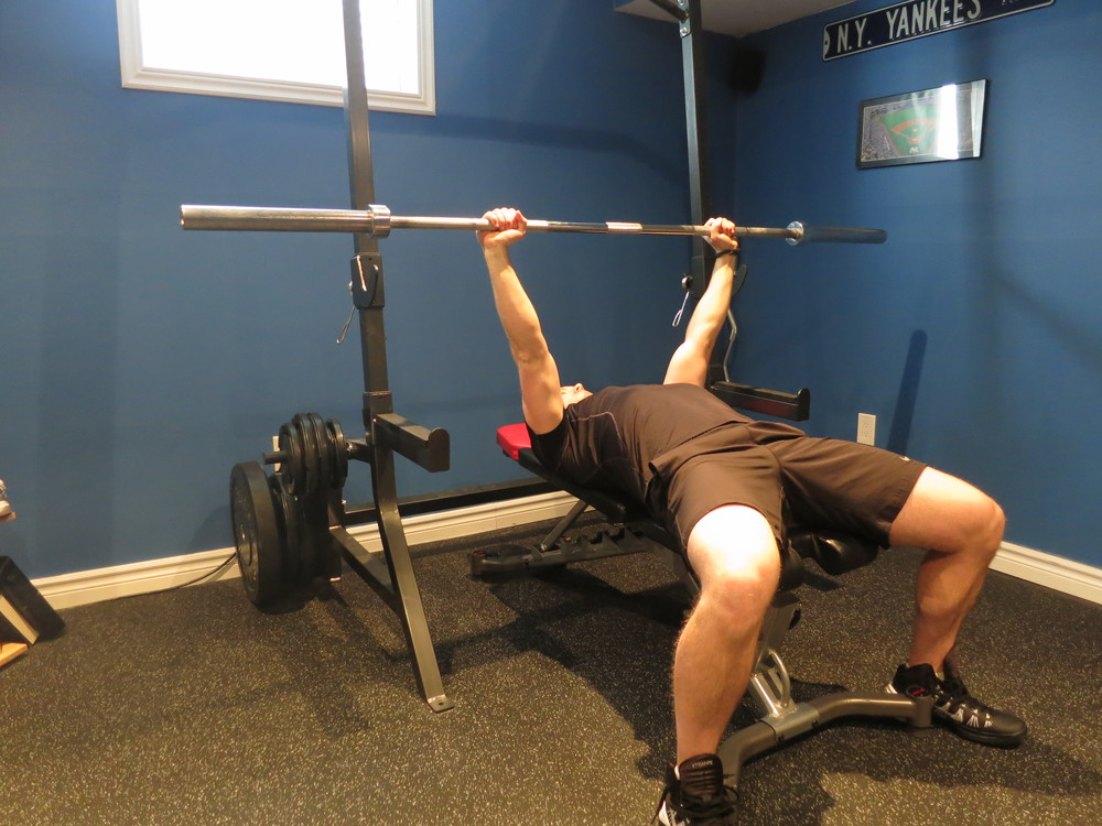 You should have a sturdy bench positioned so that when you are laying down, your feet can be flat on the ground. Maintain 5 points of contact throughout: 2 feet on ground, glutes, upper back, and back of head on bench.